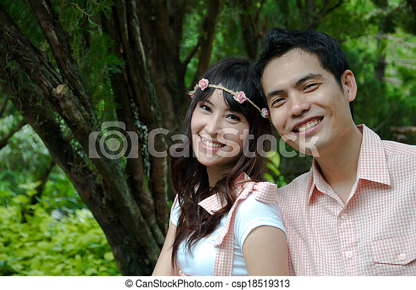 Portrait of a happy couple laughing at camera - csp18519313
