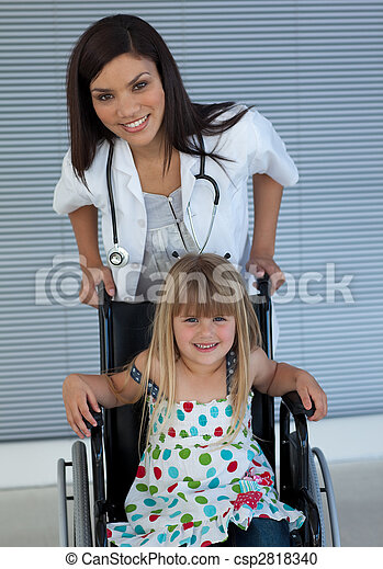 Portrait of a little girl on a wheelchair and a young doctor - csp2818340