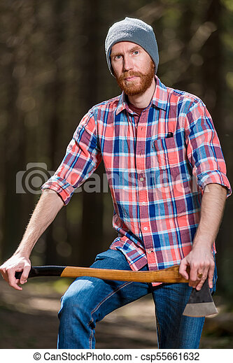 c7e83c461b8 Portrait of a man in a plaid shirt with an ax in the forest.