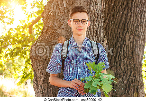portrait of a man in glasses nerd on a tree background - csp59090142