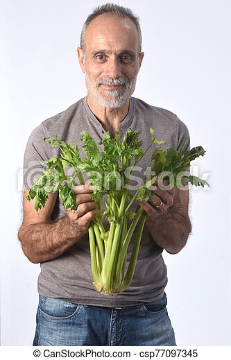 portrait of a man with celery on white background - csp77097345