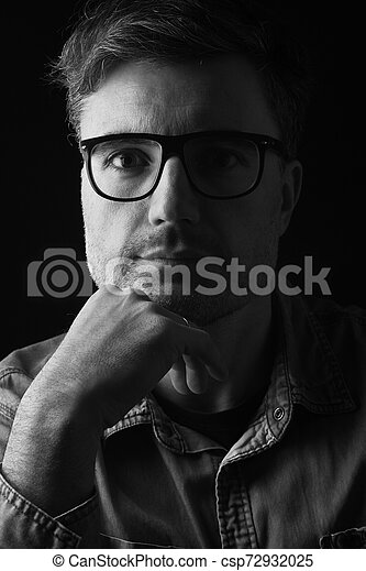 portrait of a man with glasses on black background - csp72932025