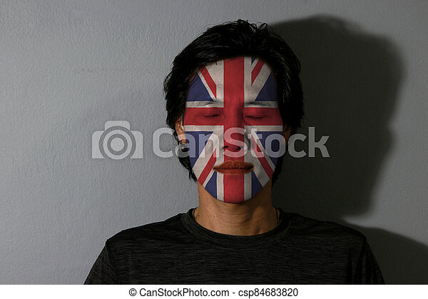 Portrait of a man with Union jack flag painted on his face and close eyes with black shadow on grey background. The concept of sport or nationalism. - csp84683820