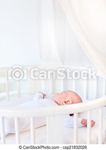 Portrait of a newborn baby boy sleeping in a white round crib wi - csp21832026