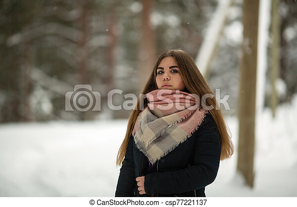 Portrait of a person russian woman outdoors in the village at winter. - csp77221137