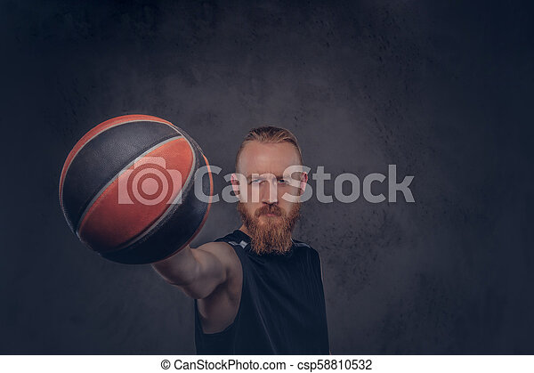 Portrait of a redhead basketball player in a black sportswear holding ball, isolated on dark textured background. - csp58810532