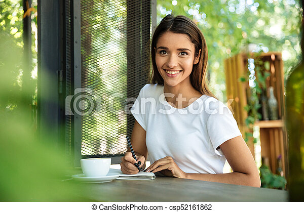 Portrait of a smiling beautiful girl making notes - csp52161862