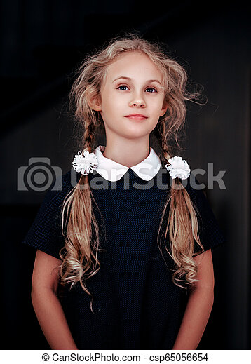 Portrait of a smiling blonde seven year old girl in school uniform - csp65056654