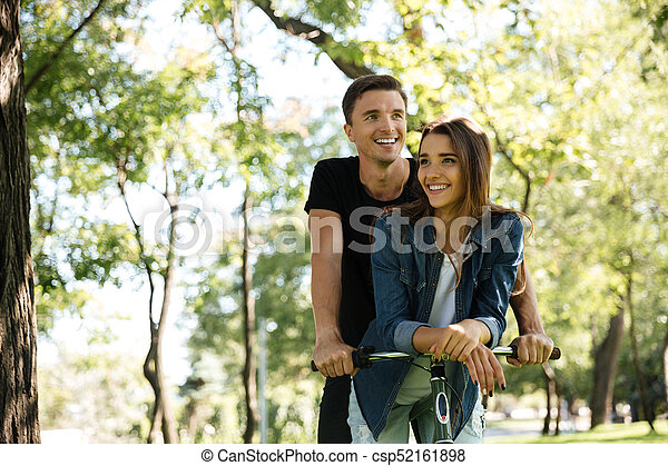 Portrait of a smiling happy couple riding on a bicycle - csp52161898