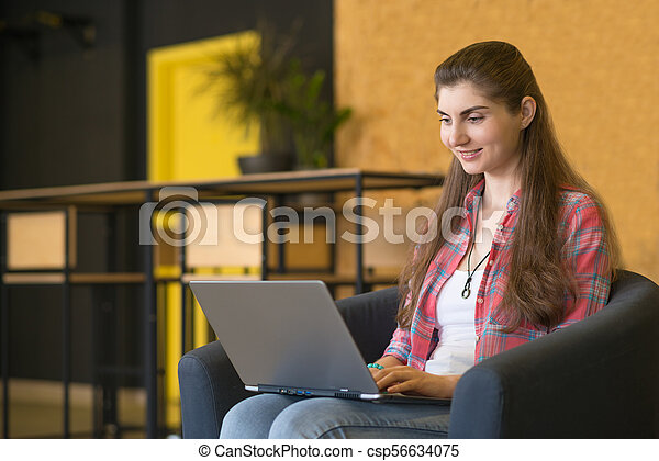 Portrait of a Smiling Woman Working on Laptop lndoors. - csp56634075