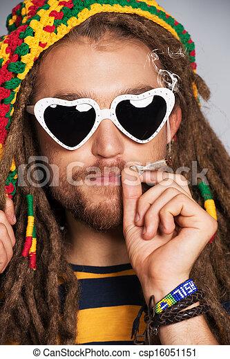 Portrait of a smoking rastafarian young man. - csp16051151
