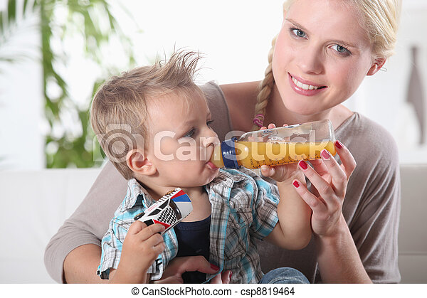 portrait of a woman feeding her son - csp8819464