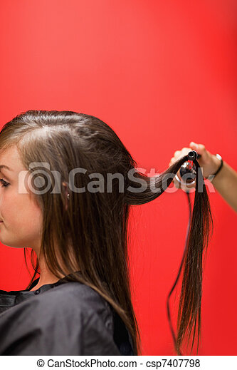 Portrait of a woman having her hair straightened - csp7407798