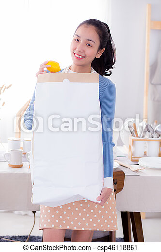 Portrait of a woman holding a paper bag with groceries. - csp46118861