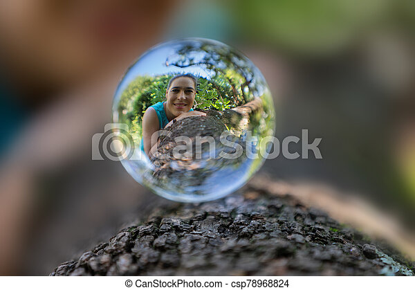 Portrait Of A Woman In Lensball On A Tree Trunk With Rough Bark Portrait Of A Woman In A Lensball On A Tree Trunk With Rough Canstock