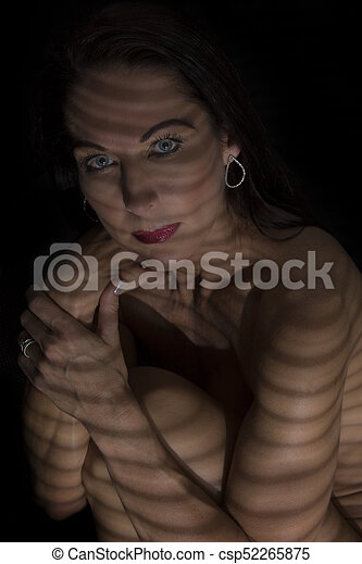 Portrait of a woman posing in darkness with shadow lines of blinds - csp52265875