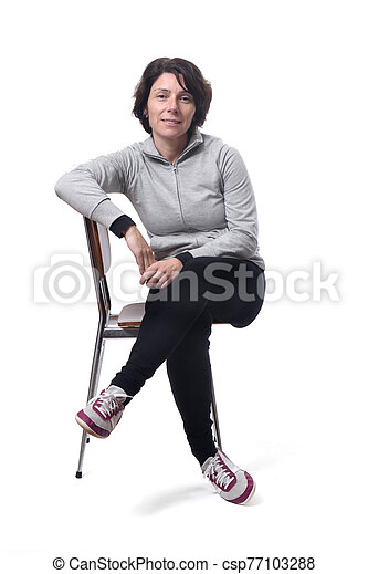 portrait of a woman sitting on a chair in white background - csp77103288