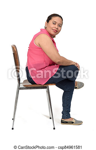 portrait of a woman sitting on a chair with the body in profile and looking at the camera on white background, - csp84961581