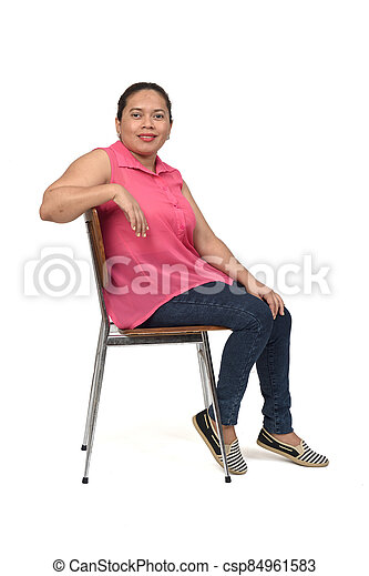 portrait of a woman sitting on a chair with the body in profile and looking at the camera on white background, - csp84961583