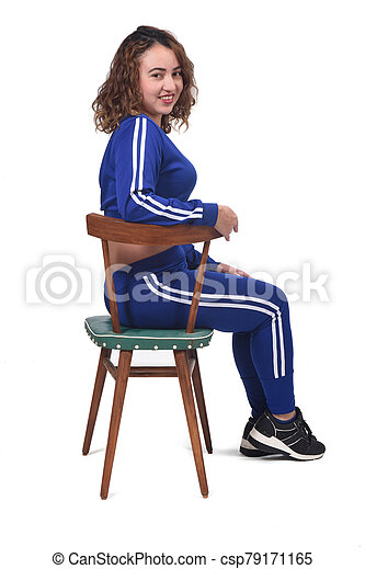 portrait of a woman sitting on a chair in white background, looking at camera, - csp79171165