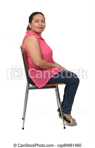 portrait of a woman sitting on a chair with the body in profile and looking at the camera on white background - csp84961460