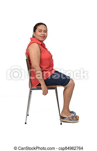 portrait of a woman sitting on a chair with the body in profile and looking at the camera on white - csp84962764