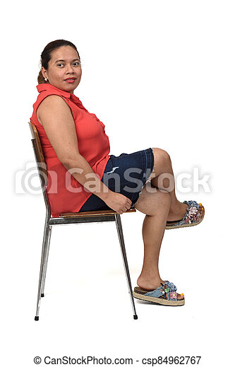 portrait of a woman sitting on a chair with the body in profile and looking at the camera on white,legs crossed - csp84962767