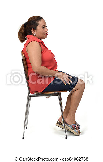 portrait of a woman sitting on a chair with the body in profile and looking at the camera on white, look side - csp84962768