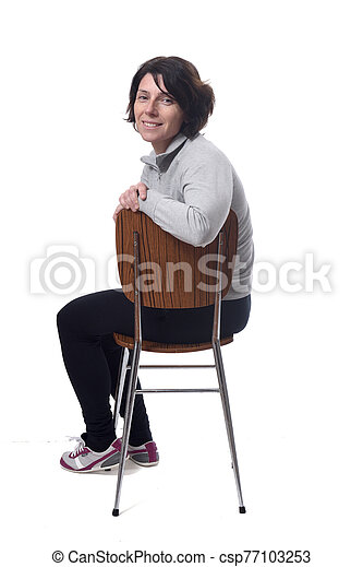 portrait of a woman sitting on a chair in white background - csp77103253