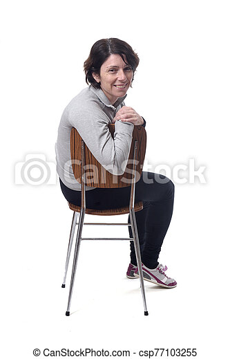 portrait of a woman sitting on a chair in white background - csp77103255