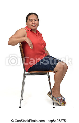 portrait of a woman sitting on a chair with the body in profile and looking at the camera on white background, - csp84962751