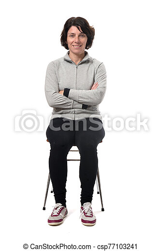 portrait of a woman sitting on a chair in white background, arms crossed - csp77103241