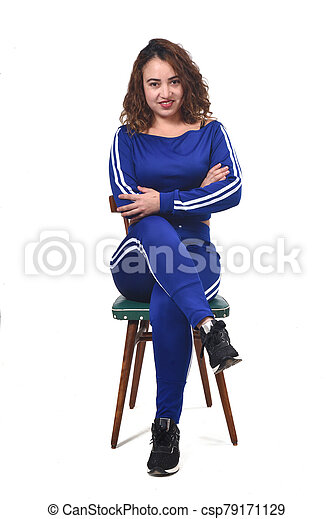 portrait of a woman sitting on a chair in white background, looking at camera - csp79171129