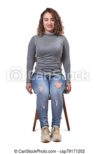 portrait of a woman sitting on a chair in white background, looking at camera - csp79171202