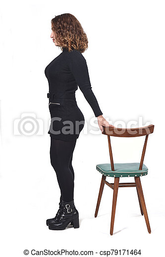 portrait of a woman standing with chair in white background, looking at camera - csp79171464