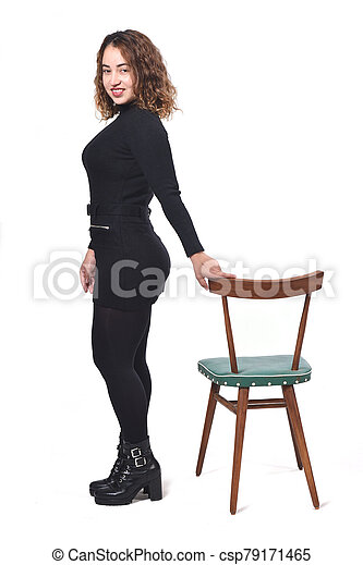 portrait of a woman standing with chair in white background, looking at camera - csp79171465