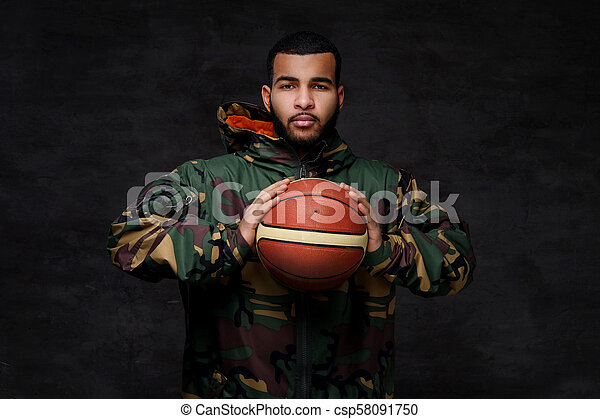 Portrait of a young African-American street basketball player in a camouflage jacket. - csp58091750