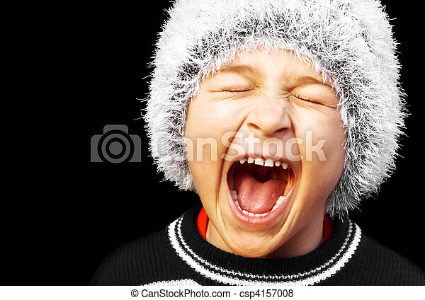portrait of a young boy screaming on black background