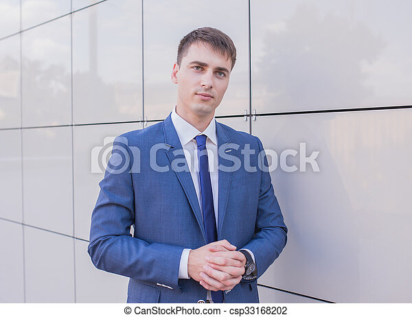 Portrait of a young businessman standing over blurred background  - csp33168202
