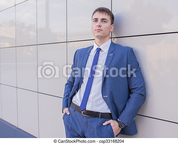 Portrait of a young businessman standing over blurred background  - csp33168204