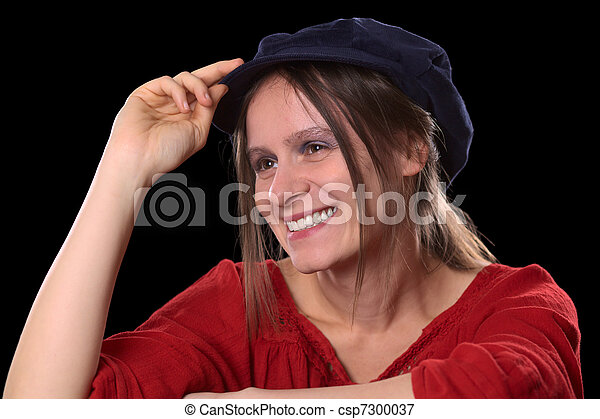 Portrait of a young Caucasian woman smiling wearing a red shirt and a blue Gatsby cap (Selective Focus, Focus on the left eye and the left side of the face) - csp7300037