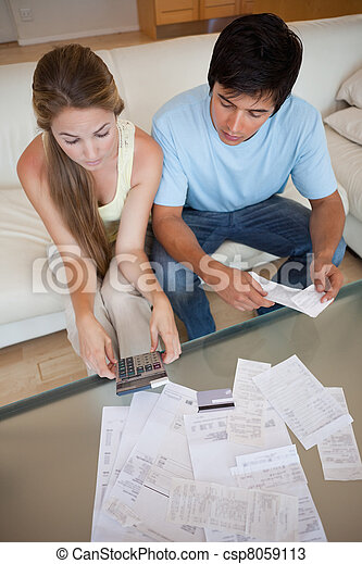 Portrait of a young couple looking at their bills - csp8059113
