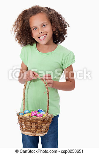 Portrait of a young girl holding a basket full of Easter eggs - csp8250651