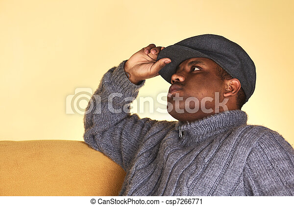 Portrait of a young man of African descent with a cap sitting on a sofa (Selective Focus, Focus on the left eye) - csp7266771