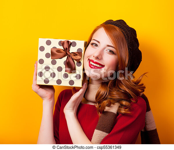Portrait of a young redhead woman with present box - csp55361349