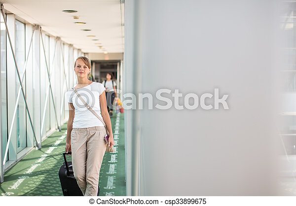 Portrait of a young woman in the boarding bridge, boarding an aircraft - csp33899675