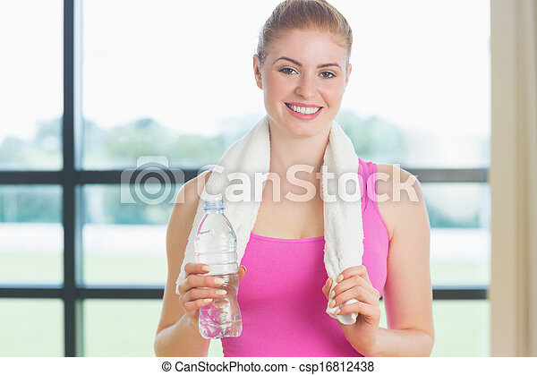 Portrait of a young woman with towel around neck holding water bottle in fitness studio - csp16812438