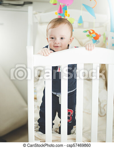 Portrait of adroable 1 year old baby boy standing in white wooden crib - csp57469860
