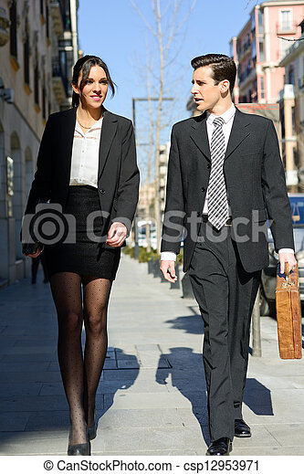 Portrait of an atractive business people walking on the street. Couple working. - csp12953971