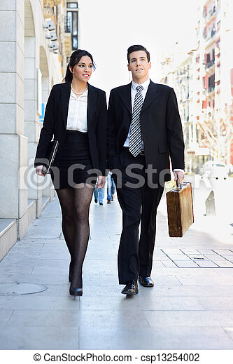 Portrait of an atractive business people walking on the street. Couple working. - csp13254002